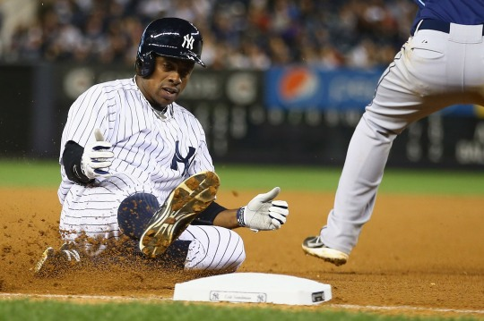 NEW YORK, NY - SEPTEMBER 25: Curtis Granderson #14 of the New York Yankees slides into third base against the Tampa Bay Rays during their game on September 25, 2013 at Yankee Stadium in the Bronx borough of New York City. (Photo by Al Bello/Getty Images)